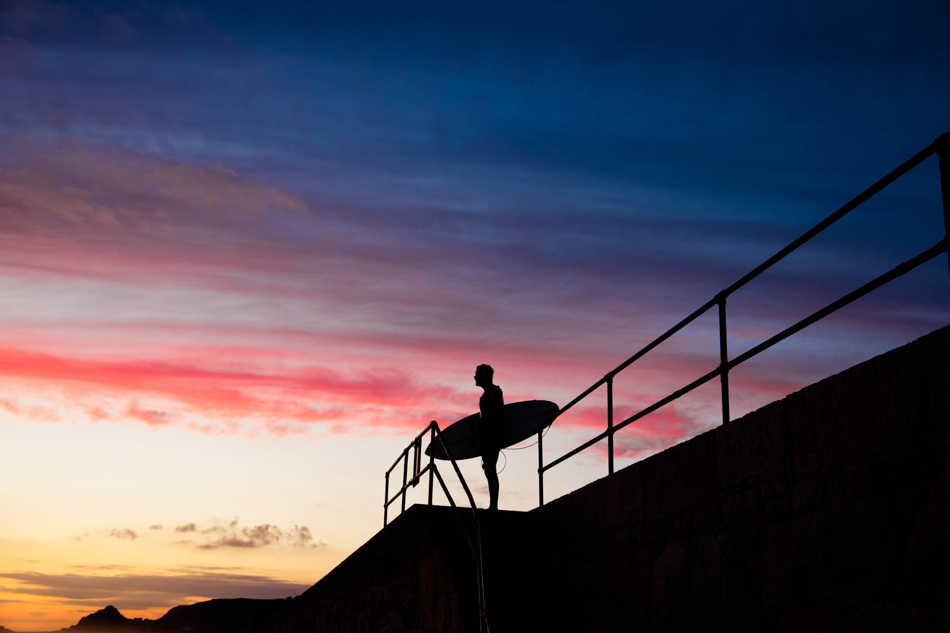 Surfer standing on seawall at St Ouen after Sunset